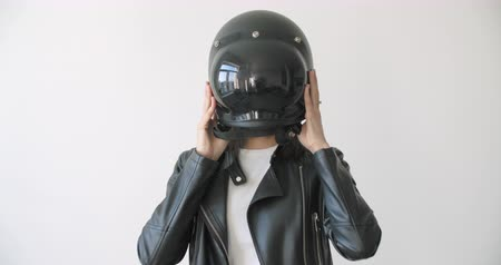 Close-up of young motorcyclist woman taking on full face helmet over white wall background