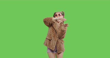 Fashion girl wearing leopard fur coat licking candy. Freak young woman with lollipop having fun . Vogue style female dancing and making scattering money signs over green screen background chroma key Stock mozgókép