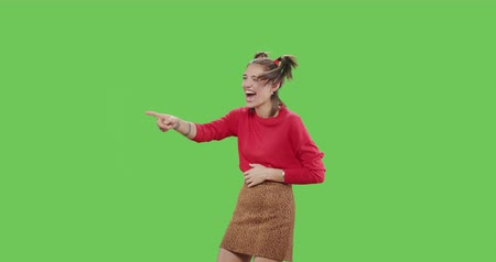 Young cheerful woman pointing to side and upwards with both hands showing object in copy space over green screen background . Girl having fun , laughing loudly , grasping at the belly on chroma key
