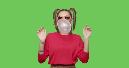 Close-up of girl wearing red jacket chewing bubble gum over green screen background, Young woman looking at camera and dancing on chroma Key . 4k raw video footage slow motion 60 fps Stock mozgókép