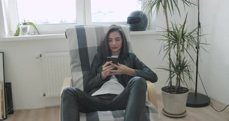 Young motorcyclist woman in black leather jacket woman sitting in a chair at home. Urban biker girl resting and using mobile phone . 4K video shooting by handheld gimbal