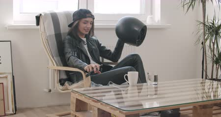 kahve molası : Close-up of Young motorcyclist woman in leather jacket put black helmet and motorcycle keys from on table. Biker girl going from walk trip ride. 4K raw video footage slow motion