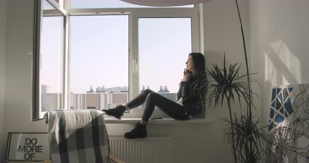 Young woman using mobile phone resting on window sill at home. 4K video shooting by handheld gimbal Stock mozgókép