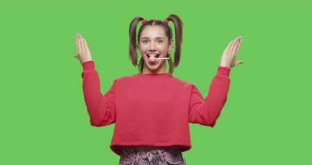 sucking : Young woman with big red lollipop close her face by hands over green screen background. Cheerful sexy girl suck and lick tasty candy, wink and flirt on chroma key