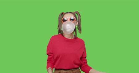 jupe : Close-up of girl wearing red jacket chewing bubble gum over green screen background, Young woman looking at camera and dancing on chroma Key . 4k raw video footage slow motion 60 fps Vidéos Libres De Droits