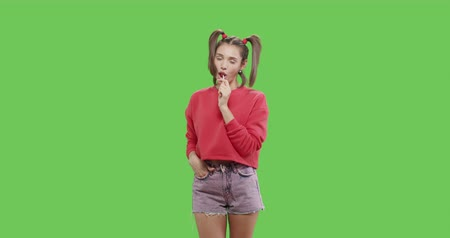 yalamak : Young woman with big red lollipop over green screen background. Cheerful sexy girl sucking licking tasty candy on chroma key. 4k raw video footage slow motion