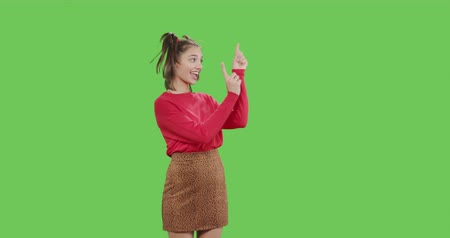 trenzas : Young cheerful woman pointing to side and upwards with both hands showing object in copy space over green screen background . Girl having fun on Chroma Key. 4k video footage slow motion 60 fps