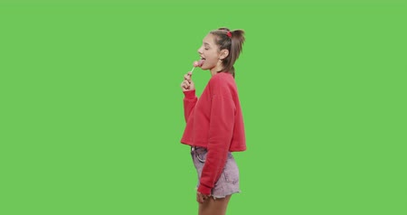 сосать : Young woman with big red lollipop over green screen background. Cheerful sexy girl stand sideways to the camera suck and lick tasty candy on chroma key. 4k raw video footage slow motion