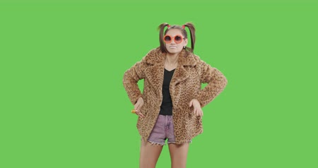 yalamak : Fashion girl wearing leopard fur coat licking candy. Freak young sexy woman with lollipop having fun . Vogue style female dancing over green screen background chroma key