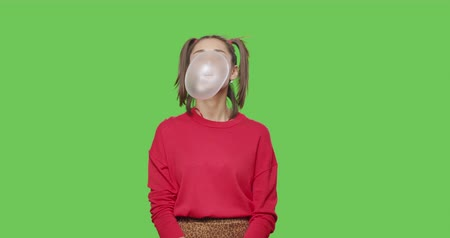 jupe : Close-up of girl wearing red jacket and sunglasses chewing bubble gum over green screen background, Young woman looking at camera on chroma Key . 4k raw video footage slow motion 60 fps Vidéos Libres De Droits