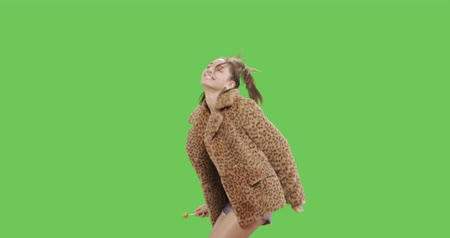 szörnyszülött : Fashion girl wearing leopard fur coat licking candy. Freak young sexy woman with lollipop having fun . Vogue style female dancing over green screen background chroma key