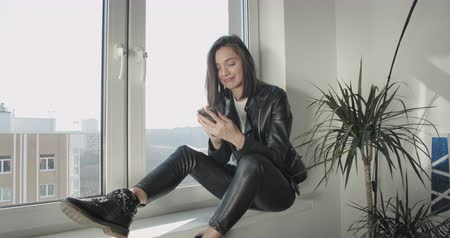 Young woman using mobile phone near window at home. Motorcyclist girl in black leather jacket texting or reading message on smartphone. Work out office . 4K raw video footage slow motion