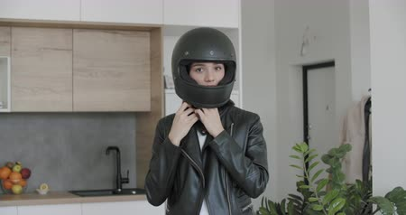 Close-up of young motorcyclist woman taking on full face helmet at home apartment background