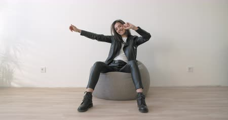 Young woman on white background. Close up of smiling girl have fun in studio. Portrait of joyful motorcyclist wearing black leather jacket and white t-shirt
