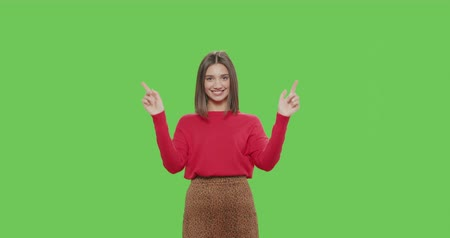 sukně : young playful woman blowing and sending air kisses to camera over green screen background. Pretty girl in red sweater and leopad skirt making sign heart shape by hand on chroma key