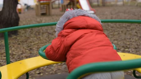 the child is spinning on the swing in the playground in the park