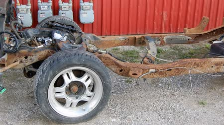hayloft : 4K Rusted Out Stripped Vehicle In Front Of Red Farm House