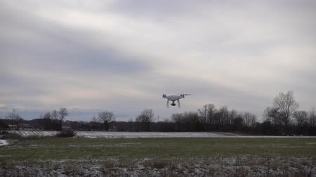 stable fly : 4K Drone Flying Around Slightly Snow Covered Field Then Flying Off