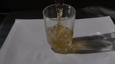 fizzing : Slow Motion Liquid Being Poured Into Glass Apple Juice Ice Tea With Droplets Stock Footage