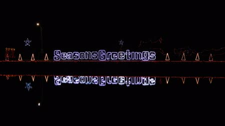 festividades : 4K Seasons Greeting Sign On Water With 3 Neon Christmas Trees Stock Footage