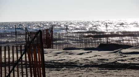 agua : 4K Waves On Bright Sunny Day With Sand And Fence