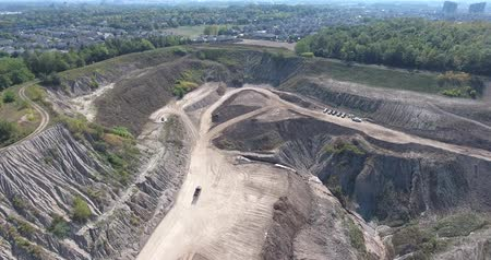 depleted : Aerial Dump Truck Driving Towards Other Trucks In Huge Gravel Pit