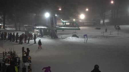 faház : Ski Chair Lifts At Night With Skiiers Getting On 4K