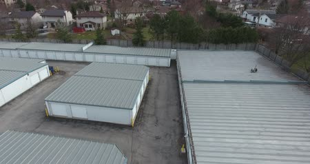 self storage : Flying Over Gray Storage Units Towards Houses Drone Aerial View