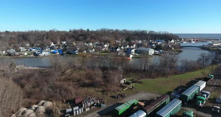 caboose : Flying Sideways Over Trains And Shipping Containers Near River 4K Aerial View