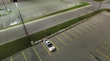 alkony : Ascending Above White Car In Empty Parking Lot Aerial View