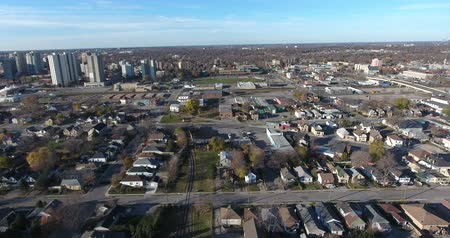 boomtoppen : Flying Over Blue Collar Neighborhood Naar Highschool Football Field 4K Stockvideo