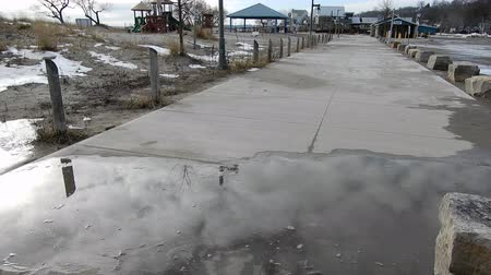 brotos : Puddle Of Water On Sidewalk Leading To Beach Restaurant In Winter Time 4K