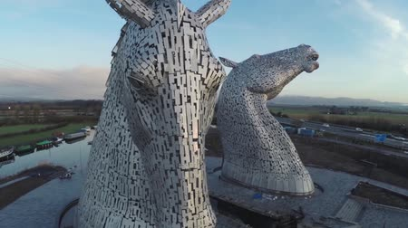 otoyol : Aerial shot of the Kelpies horse heads at the Helix park in Falkirk during sunrise Stok Video