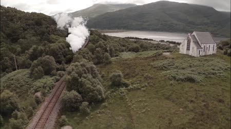 skotsko : Stunning aerial shot of the Jacobite Steam Train passing a small church set among stunning scenary in the Scottish highlands