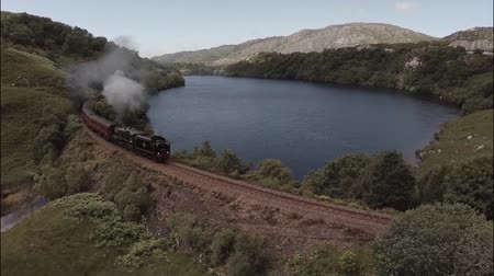 vasúti : Aerial shot of the Jacobite Steam Train passing a loch in the Scottish highlands en route to Fort William