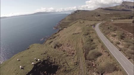 side view : Aerial shot from the Isle of Skye in Scotland, revealing the coastline with small country road to the side and the old man of Storr in the backgroun