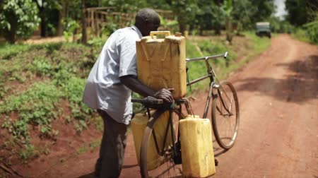 coletando : African man using a bicycle to collect water in 3 containers pushing bike Stock Footage
