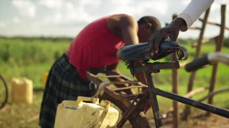 coletando : An African girl attaching water containers to a bicycle Stock Footage