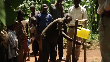 nações : An African child using a handwash station made from plastic containers