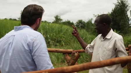 Кения : Caucasian man chatting to African man by a water well in Uganda, Africa Стоковые видеозаписи