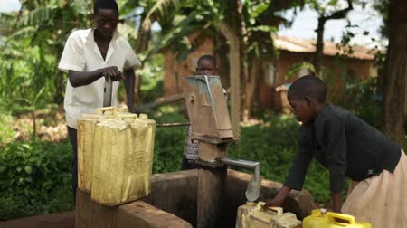 засуха : An African boy filling up yellow water containers at a well with his brothers and sisters