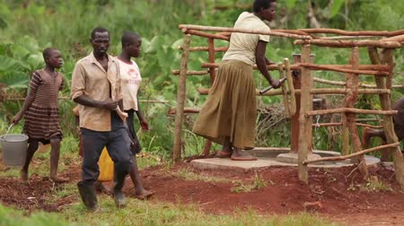 pompki : An African family filling up yellow water containers at a well