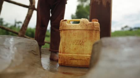 zambia : A young African child picking up and walking away with a plastic water container after filling it