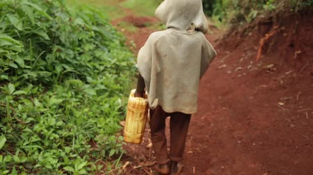 világ : A young African boy walking with a yellow water container to a well in Uganda