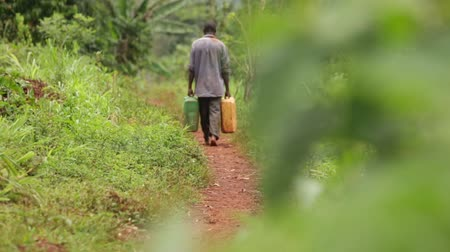 poça de água : A man walking along a rural path with 2 water containers