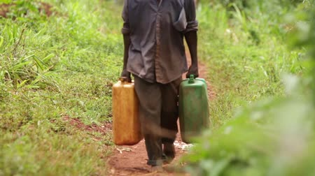 afrika : A man walking along a rural path with 2 water containers