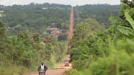 vila : A straight long road in rural Uganda with a motorbike passing by