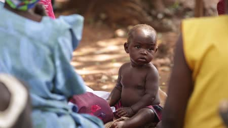 yoksulluk : A young African child sitting smiling amoung others Stok Video
