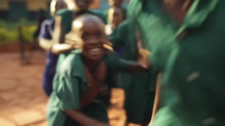 детеныш : Young happy African boys playing class at school in rural Uganda with sun flare