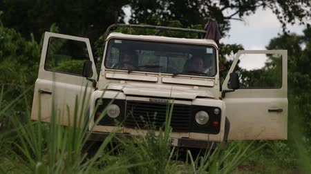 droga : Two caucasian men sit in a landrover defender with open doors in a rural setting in Uganda, Africa